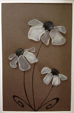 Genuine White Sea glass collected from a beach on the coast of California arranged into a collage of flowers with beach pebbles as centers with a brown background. Framed and matted in a 9 x 7 black frame. #seaglass