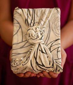 Faça uma embalagem de presente com um lenço de pano. Fica genial.