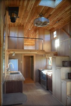 Tiny house with wood ceiling, storage in the staircase, sleeping loft, and open kitchen.