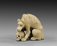 ANTIQUE IVORY NETSUKE: Wolf & Skull Large and finely detailed, antique ivory (probably marine), okimono-sized netsuke; of a wolf with inlaid eyes, hunched over and with one paw on a skull; unsigned, 19th Century