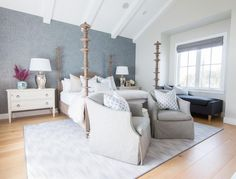 Under a white vaulted ceiling with white wood beams, a gorgeous Noir Ferret Weathered Bed is dressed with cream colored duvet covering white sheets accented with white shams sat behind cream and light blue pillows.