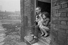 Vater und Tochter sitzen mit ihrem Hund auf den Stufen ihrer Unterkunft im Bezirk  Liverpool 8 , 1969. Die Initiative Shelter feiert in diesem Jahr ihr 50-jähriges Bestehen.