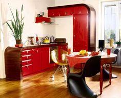 Drewniany stół reprezentuje zupełnie inną epokę, ale krzesła są zdecydowanie w duchu lat 50. Niebieskie powstało nawet w tym okresie - to tzw. panton (od nazwiska projektanta Vernera Pantona).