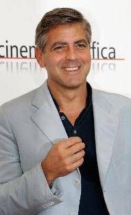 George Clooney wearing light gray suit and black polo shirt