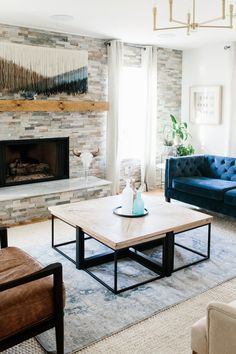 blue velvet tufted sofa, boho tapestry, stone fire place and brass fixtures