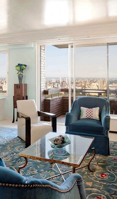 Living room decor with hand-wrought iron coffee table in antiqued gold  leaf finish and blue armchairs; luxury apartment living ideas; appartment furniture inspiration