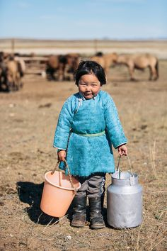 A Mongolian girl carrying milk in buckets, The Mongolian Steppe, Dashinchilen, Mongolia