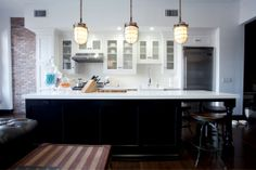 loft kitchen images | Loft kitchen with dark black island, light quartz countertops and ...