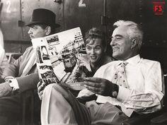 """Dal set """"La Baia di Napoli"""" con Clark Gable e Vittorio De Sica che legge la rivista aziendale FS """"Voci della Rotaia"""", durante una pausa delle lavorazioni."""