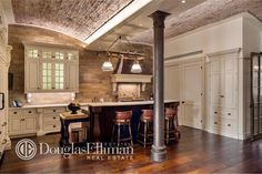 Arched brick ceiling in kitchen with white dividing wooden panels and stone walls