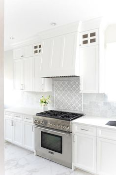 A stainless steel oven range sits beneath white and gray mosaic cooktop tiles framed by mini brick marble backsplash tiles mounted under a white wood paneled hood. Stove Backsplash, White Kitchen Backsplash, Kitchen Hoods, Kitchen Stove, Kitchen Countertops, New Kitchen, Backsplash Ideas, Beach House Kitchens, Grey Kitchens