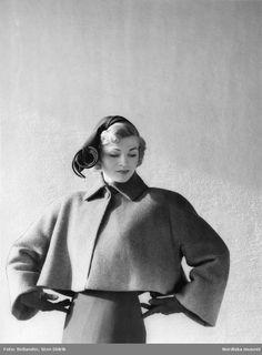 Modebild. Kvinnlig modell i dräktjacka och hatt. Fotograf: Sten Didrik Bellander, 1949-1951