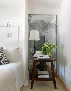 I love the idea of a simple nightstand—backed by a beautiful antique mirror—leaning against the wall.