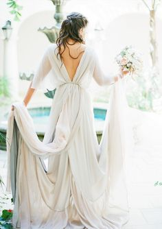 A bride wears a handmade wedding dress with an open back and long train
