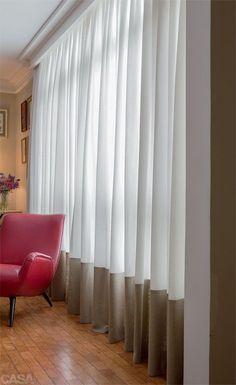 """A elegância da barra alta - Uma proposta pouco convencional foi adotada pelo designer Paulo Rossi, da Interiores Confecções, para fechar o vão de 4 m de largura por 2,70 m de altura da janela de sua sala: barra dupla de 60 cm de altura e de cor diferente do restante da cortina. """"Repeti ali o tom da parede, que é neutro e não interfere na decoração"""", afirma. No barrado, ele usou linho sintético, enquanto o resto da peça é de xantungue misto de seda e poliéster. """"São duas texturas diferentes…"""