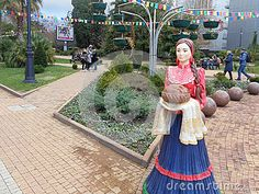 Russian hospitality, sculpture Cossack woman with loaf, walking area with flower beds and palm trees, resort Sochi, Russia