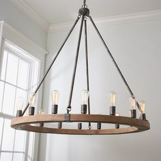 A handcrafted massive wooden ring hangs from a minimal metal frame creating an industrial piece with urban vibes. The large scale and open body will appeal to a two-story foyer, large dining room or great room setting with ease.