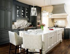 Gorgeous two tone kitchen design with charcoal gray kitchen cabinets, white kitchen island & calcutta gold marble counter tops