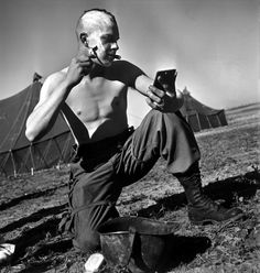 Robert Capa - France. Arras. March 23rd, 1945. An American paratrooper shaving his head Mohawk-style for good luck and esprit de corps.