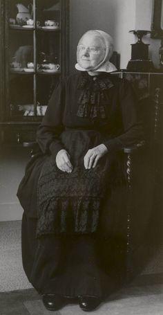 Mevrouw Risseeuw-Tromp in Cadzandse streekdracht. Mevrouw Risseeuw woonde in Middelburg en is 80 jaar op het moment dat de foto werd gemaakt. Ze draagt een schootjak met rok en een schortje met broderie-borduursel. Op het jak draagt ze een zwart kanten jabot. Onder de kanten cornetmuts draagt ze een zwarte ondermuts met mutsenbellen, die nog juist zichtbaar zijn in de voorstrook van de cornetmuts (ter hoogte van de mond).  #Cadzand