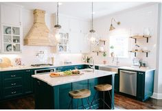 Simplistic kitchen with bubble lanterns. So bright. Love the navy-green underneath the counter space! @joannagaines_