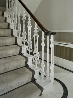 Stair detail in Entrance Hall. Stair runner with trim. Marble floor with border. Radiator box, Ornate ironmongery on stairs, wood handrail.