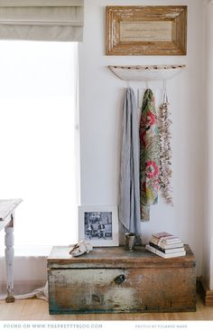 Vintage wooden chest, weathered picture frame, and floral scarves give a room character.