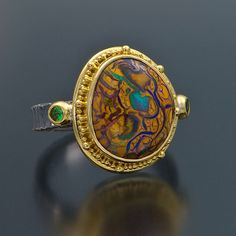 Gorgeous one-of-a-kind Australian Yowah opal ring set in 22K yellow gold with two tsavorite garnets on the side. Band is hand-forged in oxidized silver.