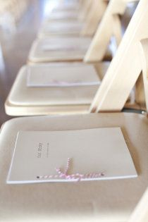 """Our Story"" on the seat of each chair. A really cute idea and something to look through while the guests wait for the ceremony to begin! And you could even do a his and her version....this wedding has so many cute and classy things!!"