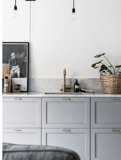 light kitchen with brass tap and marble worktops details. Kitchen styling with green plants and posters. Nordic Design, Work Surface, Grey Cabinets, Modern, Double Vanity, Grey Kitchens, Counter, Marble, Designer