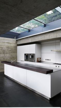 Concrete and timber beams combine with the natural elements of this kitchen to create an urban and rugged look.