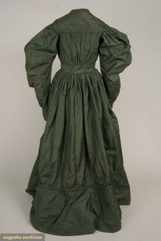"""BOTTLE GREEN SILK FAILLE DRESS, LATE 1820s Front opening gathered bodice with high rounded neckline and top yoke effect, corded self fabric trim, 1.75"""" inset waistband, long sleeves, full at top and gathered, narrowing to 3.5""""-4.5"""" tapered cuffs, full pleated skirt gathered and attached to bodiceback, apron front hooking to bodice waistband, deep flounced hem with piping and down padded hem under flounce, glazed linen bodice and skirt lining, cuffs lined in silk, flounce lined in brown…"""
