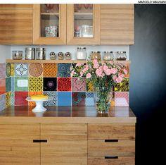 O painel com azulejos da Calu Fontes criado acima da bancada deixa a cozinha mais divertida. Projeto da arquiteta Gabriela Marques.