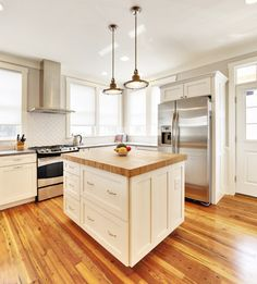 White and wood square kitchen island. Simple and contrasts beautifully with the wooden floor beams.