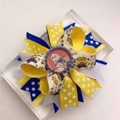 This Minion - Boutique Hair Bow measure approximately 5 inches across. • Alligator clip ( can be changed to French Barrete upon request) Also available on a stretchy headband ( please message me ). Lots of layers of ribbon are topped off with a cute little minion bottle cap.  •All ribbon ends are heat sealed to prevent fraying. Like my Facebook page & follow my work. Thank you!  www.facebook.com/AurorasChicBowtique