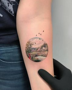 Landscape circle tattoo on the left inner forearm.