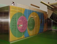 """Glass Donor Wall: The highest level donors are etched into tinted glass panels while lower level donor names are silk screened on changeable panels. The colors are derivative of the colorful environment. The circle pattern reinforces the """"Circle of Hope"""" tag line used by Focus Hope."""