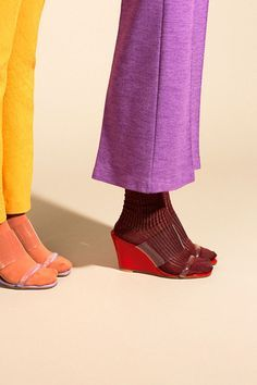 bright coloured fashion. Purple trousers, winer coloured socks and red and clear plastic shoes. Yellow trousers with orange socks and pink shoes
