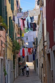 Clothes drying and children playing in a narrow street in the Castello area of Venice, Italy
