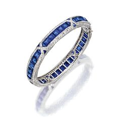 SAPPHIRE AND DIAMOND BANGLE-BRACELET The hinged hoop set with segments of square-cut and triangular-shaped sapphires within borders of numerous small round diamonds, the total diamond weight approximately 9.00 carats, mounted in 18 karat white gold. [Ooo, I want!]