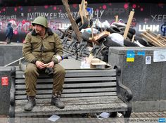 "UKRAINE, Kiev : An activist wearing a military helmet guards a barricade put up by opposition protesters in the center of Kiev on December 19, 2013. President Viktor Yanukovych told the West today to stay out of Ukraine's political crisis, as Russian President Vladimir Putin said Moscow had offered Kiev a multi-billion dollar bailout package to help a ""brotherly country"" out of trouble. AFP PHOTO / YURIY DYACHYSHYN"
