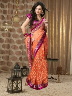 Buy Wedding Sarees Online | Go with the latest fashion trend in this orange net saree by kalazone. The saree has golden zari buttys all over the patli. The pallu has designer motifs on it and the dual heavy border on either side of the saree gives it a gorgeous look. It is teamed with a contrasting pink designer blouse enhancing the beauty. (Slight variation in color is possible) Buy Now - http://www.kalazone.in/ratan-chandan.html