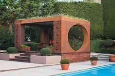 Metal laser cut pergola by the pool by Entanglements metal art. Rust finish