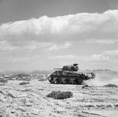 A Sherman tank advances at speed in the Foudouk Pass, Tunisia 8 April 1943.