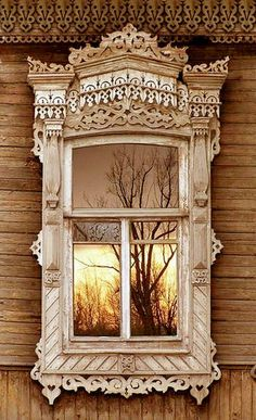 Russian wooden house, window with carved platband