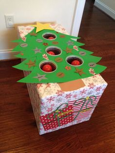 Christmas tree ball toss for a preschool holiday game--For math I would put numbers by each slot so they could add up their scores!