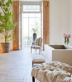 Baño ecléctico donde la madera lavada del suelo y las paredes desnudas acogen una selección de antigüedades y árboles con una intención de atemporalidad.