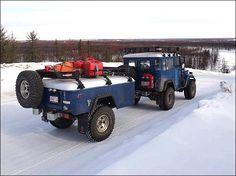 Blue Toyota FJ40 Land Cruiser with FJ40 styled camping trailer.