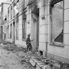 A soldier of 6th King's Own Scottish Borderers, 15th (Scottish) Division, searches wrecked buildings in Blerick, a suburb of Venlo in The Netherlands, 5 December 1944.