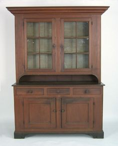 "Pennsylvania poplar two part Dutch cupboard, probably Chester County, ca. 1810, the bold ogee molded cornice over 2 glazed doors and molded edge pie shelf, resting on a base with 3 drawers and 2 cupboard doors, supported by spurred bracket feet, retaining an old red stained surface, and an ivory interior with plate rails and spoon rack, 83 1/2"" h., 56"" w. Provenance: Edgar & Charlotte Sittig."